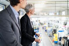 Two business people looking over a manufacturing plant