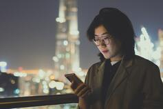 Girl wearing spectacles looking at mobile at night