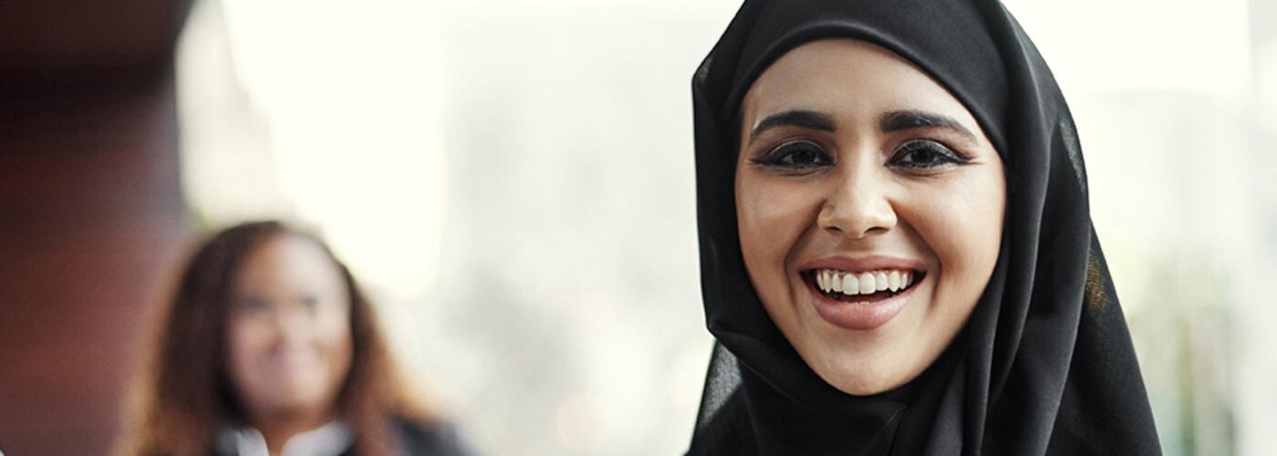 Arab woman wearing black with people in blur background