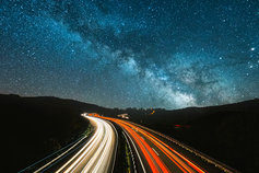 Blurred traffic under starry night sky