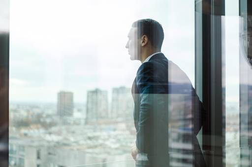 Business man looking out from office balcony
