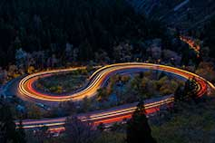 Car headlights illuminate winding road in Big Cottonwood Canyon