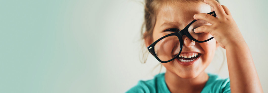 Little girl laughing while trying on glasses