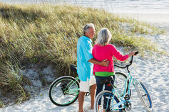 Middle aged couple at the beach with their bikes