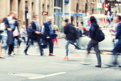 People crossing city street during rush hour