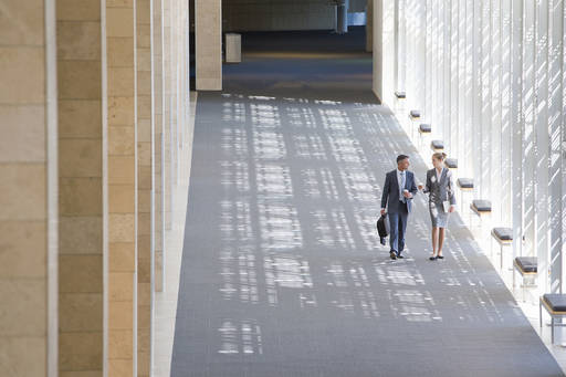 Two business people walking through modern office