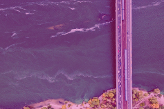 Aerial view of bridge over water with pink overlay