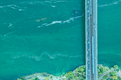 Aerial view of bridge over water with teal overlay