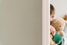 Boy with teddy bear peaking around a doorway