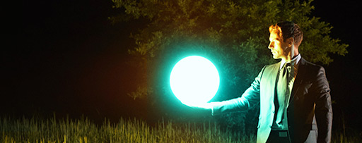 Business man holding up a glowing ball