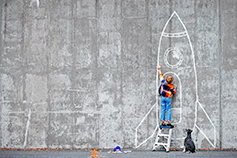 Child drawing a rocket on a wall using chalk