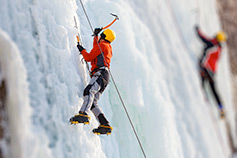 Climbers climbing up a frozen waterfall