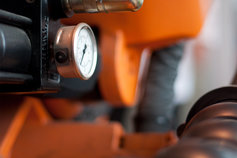 Close up of orange machinery and gauge