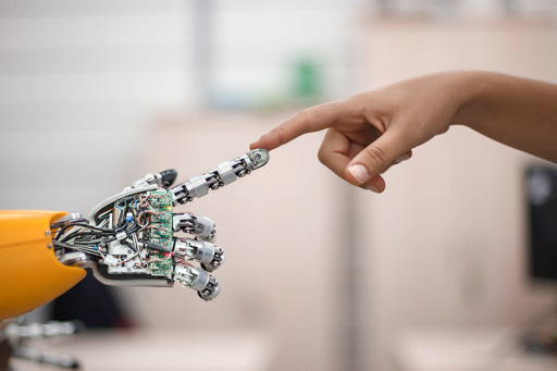 A human hand reaching one finger to touch the finger of a robot hand