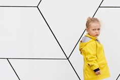 Young girl in a yellow raincoat against a white wall