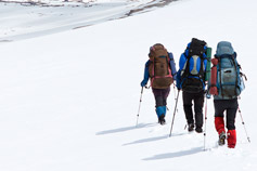 Group of mountaineers walking through snow-covered mountains