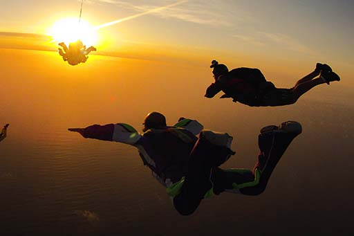 Skydivers against a sunset