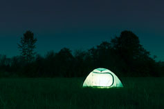 Illuminated tent in field at night