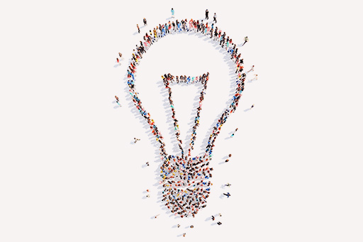 Large group of people gathered together forming a shape of a light bulb