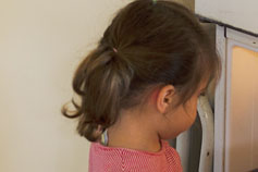 Little girl looking inside fridge