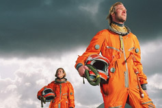 Man and woman wearing space suits standing on rugged landscape