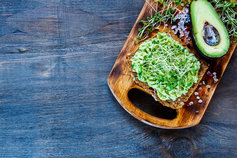 Smashed avocado on toast served on a chopping board