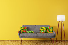 Sofa with flower pattern cushions next to floor lamp
