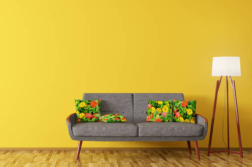A grey couch with floral cushions, floor lamp against a yellow wall. Mid-century modern style