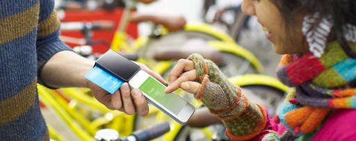 Woman using mobile in a bicycle shop