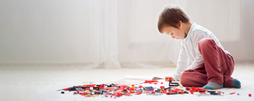 Young child playing with colourful building blocks