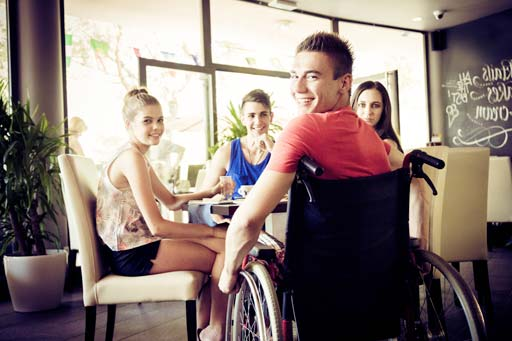 Young disabled man with his friends at a cafe