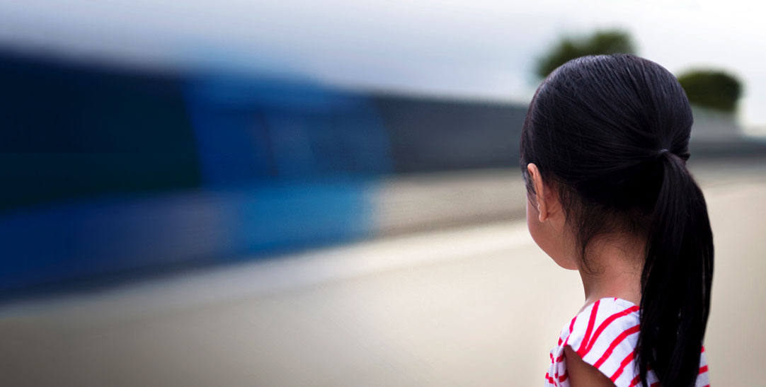 Young girl looking away at moving train