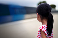 Young girl looking at moving train