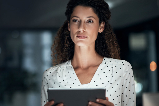 A businesswoman reflecting while using her tablet