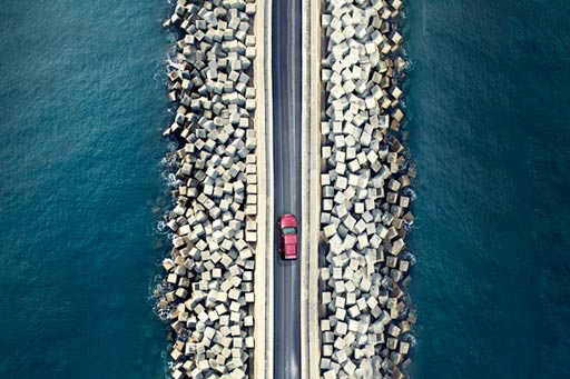 Aerial view of car driving along the coastline
