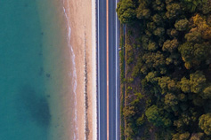 Birds-eye view of a road between a mountain and the ocean