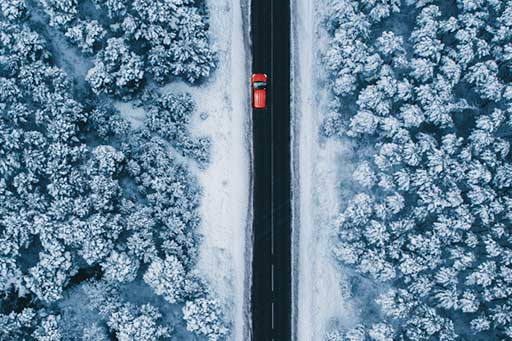 Aerial view of a red car on a road through snow-covered trees