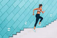 Athletic woman running up outdoor stairs