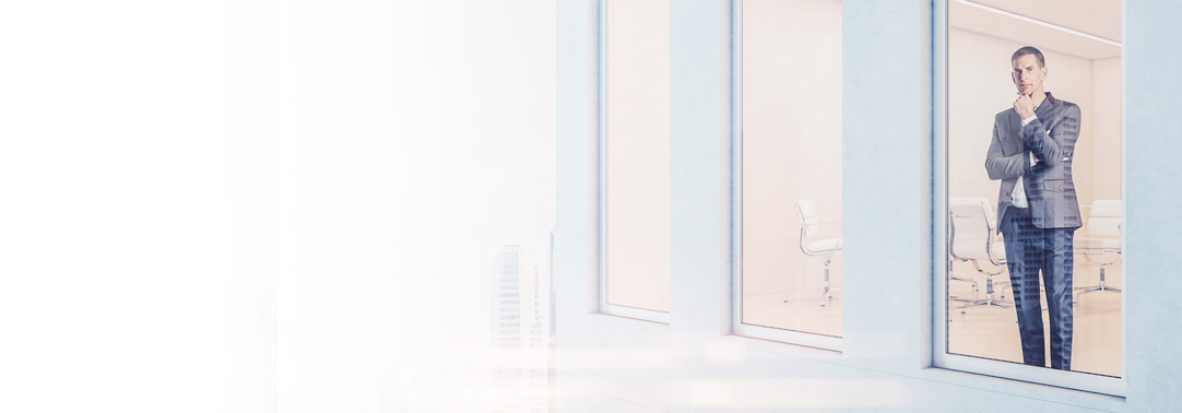 Businessman standing at window of high-rise building
