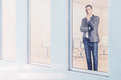 Businessman reflecting and looking out from office window