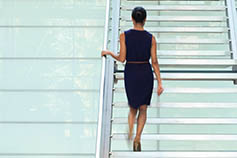 Businesswoman walking up a staircase