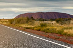 Close-up of road with Uluru in the background