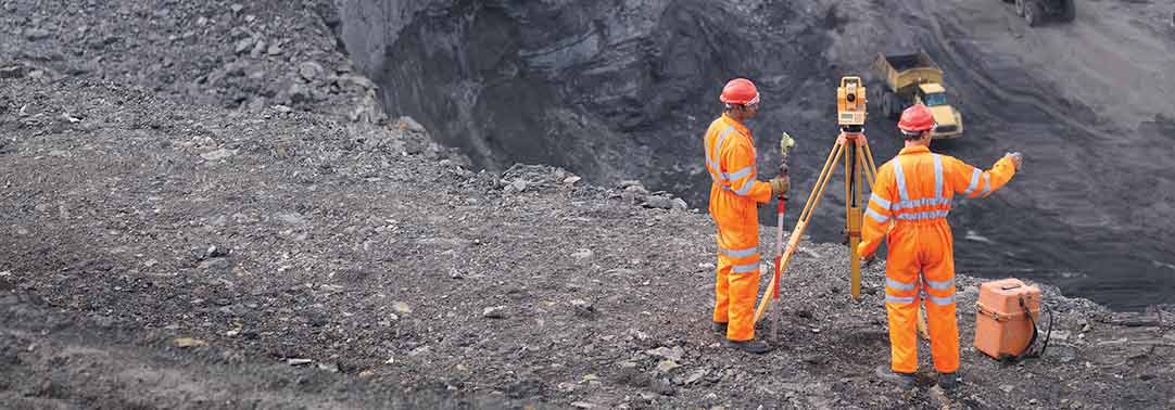 Two workers in orange uniform at mining site