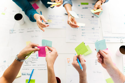 Colleagues using post-it notes during a brainstorming meeting