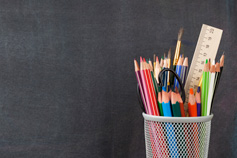 Coloured pencils and stationery in a mesh cup holder on a charcoal background