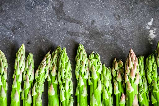 Fresh asparagus lying on a grey stone benchtop