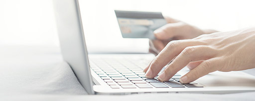 Hands typing on laptop and holding credit card