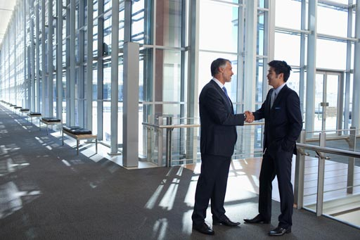 Businessmen shaking hands in modern lobby