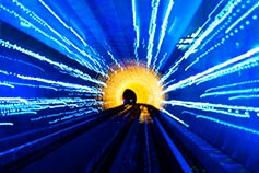 Train tunnel illuminated with blue and yellow