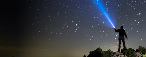 Man on top of mountain illuminating the night sky with a blue light
